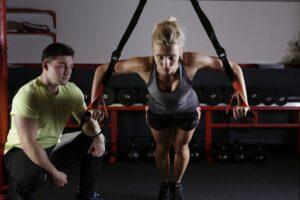 kobieta z trenerem ćwicząca na siłowni